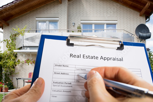 Photo Person Hand Filling Real Estate Appraisal Document