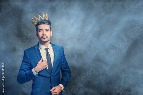 Fotografie, Obraz  Young attractive man in a blue suit with a crown on his head in the smoke