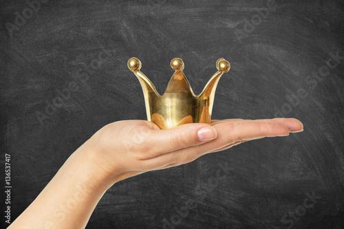 Goldene Krone auf Hand vor Schultafel