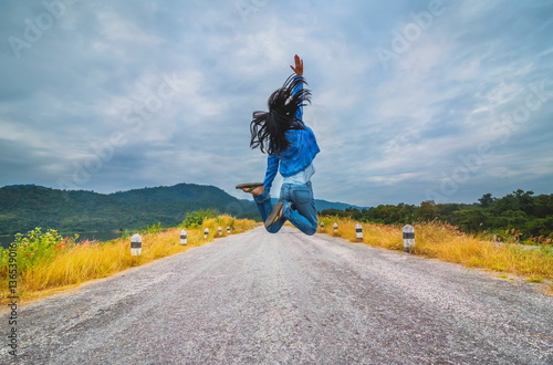 Beautiful girl jumping on the rural road