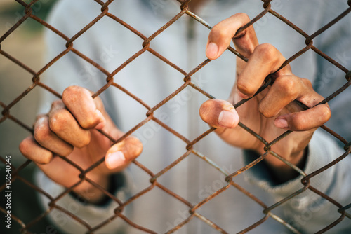 Fotografie, Obraz  young man behind cage