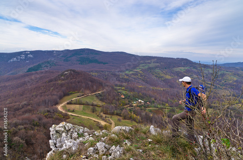 Plakat  A hiker at the rock watching winding mountain road below, Homolje mountains, eas