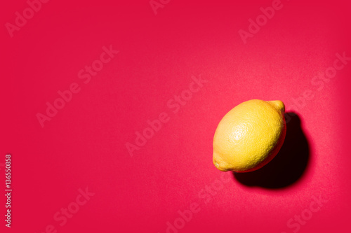 Isolated lemon projecting shadow on red background - 136550858