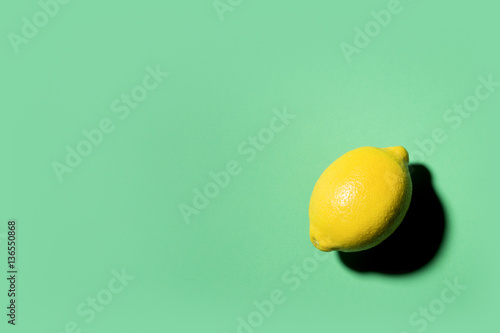Isolated lemon projecting shadow on green background