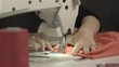 Close up footage of sewing machine stitching piece of peach-colored fabric while woman's hands holding it on table in slowmotion