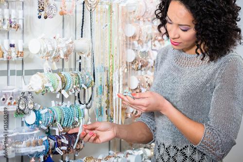 Fotografie, Obraz  Junge Frau sieht sich Schmuck in einer Boutique an