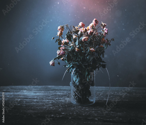 Dried bunch of roses in a vase on a wooden table on a black and blue background. Concept: dead flowers Wall mural