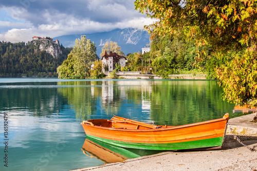 pomaranczowo-zielona-lodka-na-brzegu-jeziora