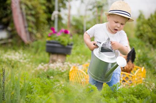 sliczne-male-dziecko-z-konewka-w-ogrodzie-podlewajace-kwiaty