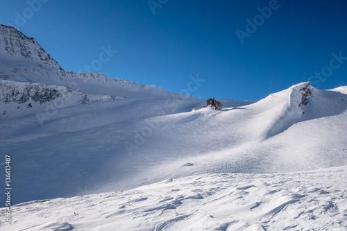 Fotografia, Obraz  Alpine refuge below mountain ridge in winter on windswept snow u