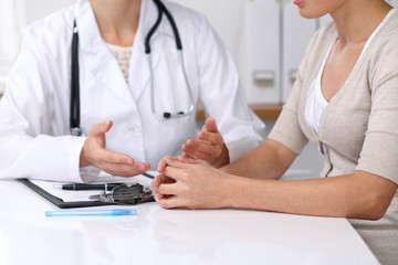 Close up of doctor and  patient  sitting at the desk while physician pointing into medical form hystory. Medicine and health care concept