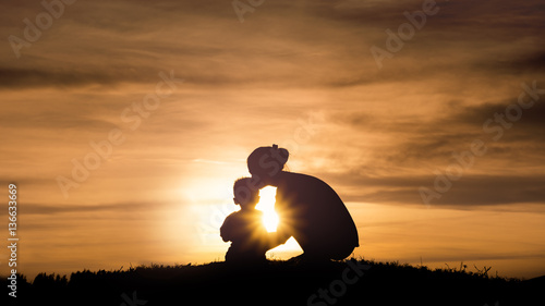 Fototapeta Silhouette of a young mother lovingly kissing her little child o obraz