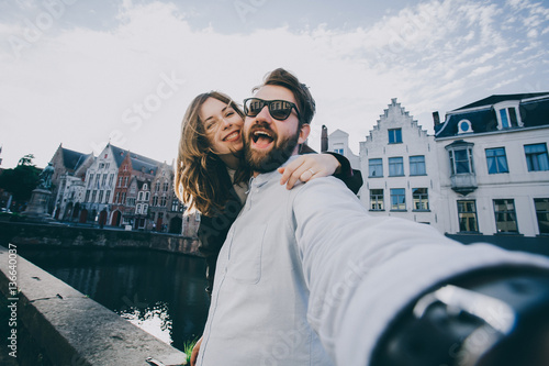 In de dag Brugge Happy young couple in love takes selfie portrait on the main street of Brugge or Bruges, Belgium. Pretty tourists make funny photos for travel blog in Europe.