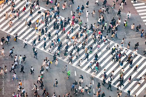 Plakat Piesi przekraczają skrzyżowanie ulic w Tokio w Japonii