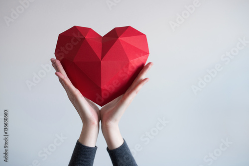Fotografia Two female hands holding red polygonal paper heart shape