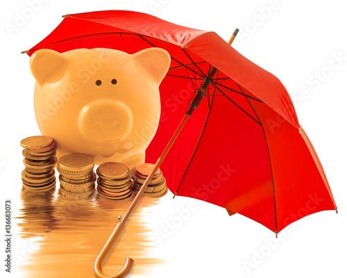 Valokuva  tirelire et argent sous parasol rouge, concept protection de l'épargne