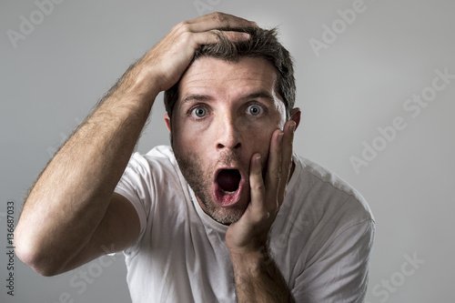 Fotografija  young attractive man astonished amazed in shock surprise face expression and sho