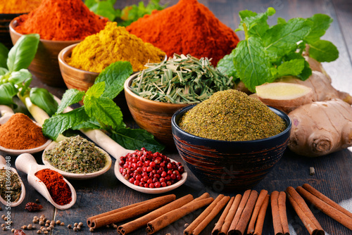 Photo Variety of spices and herbs on kitchen table