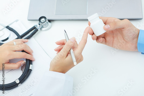 Fotografia  Female medicine doctor hands hold jar of pills and explain the patient how to us