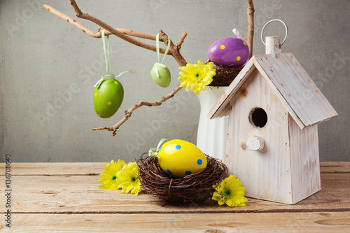 Easter holiday concept with eggs decorations and bird house over rustic backgrou Wallpaper Mural