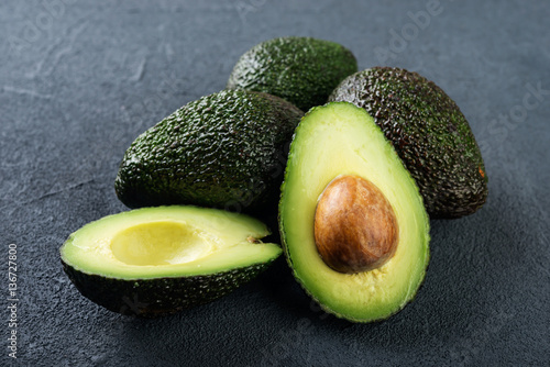 Fresh avocado on dark background. Vegetarian  food concept. Selective focus