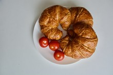 Three Croissants With Tomatoes On The White Plate On The White Table