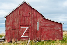 Facade Of Red Wooden Old Barn With Big White Z On The Door.