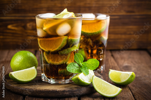 Photo  Cuba Libre cocktail with cola, lime and ice in glass, cold longdrink