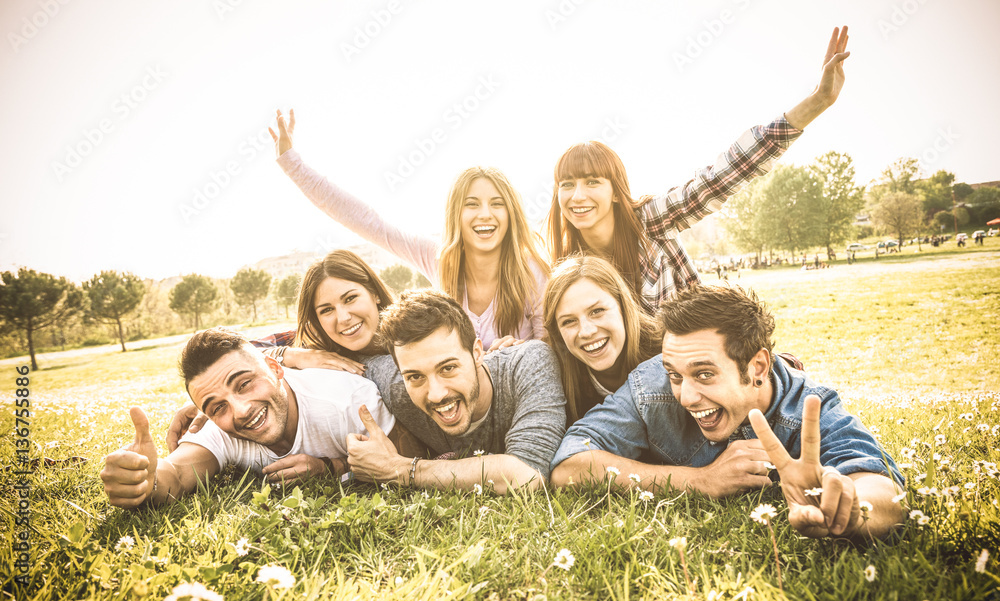 Fototapeta Friends group having fun together with self portrait on grass meadow - Friendship youth concept with young happy people at picnic camping outdoor - Warm vintage filter with backlight contrast sunshine