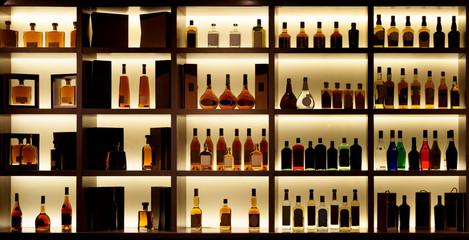 FototapetaVarious alcohol bottles in a bar, back light, logos removed