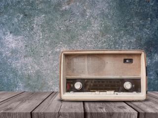 Fototapeta na wymiar Old retro radio on wood table with concrete background