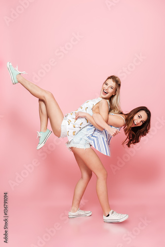 Fotografia  Cheerful woman holding her friend on back and having fun