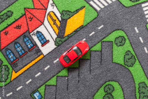 Red toy car on a city themed carpet, city street concept