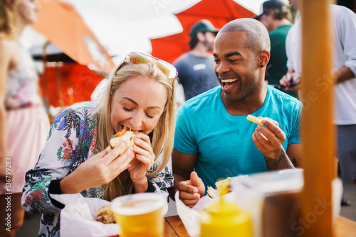 Keuken foto achterwand Kruidenierswinkel couple having fun time eating burgers and drinking beer