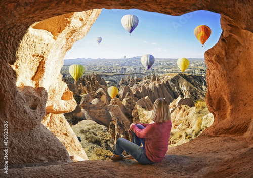 Poster Turquie Woman watching like colorful hot air balloons flying over the valley at Cappadocia, Turkey. Volcanic mountains in Goreme national park