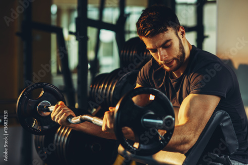 Fototapeta Handsome man doing biceps lifting barbell on bench in a gym obraz