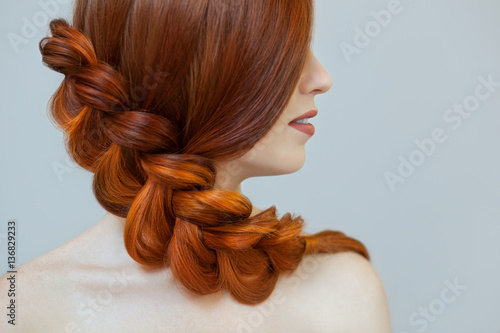 Fényképezés  Beautiful girl with long red hair, braided with a French braid, in a beauty salon