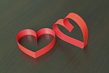 Two Red Hearts Made Of Paper Strips On A Black Wooden Background