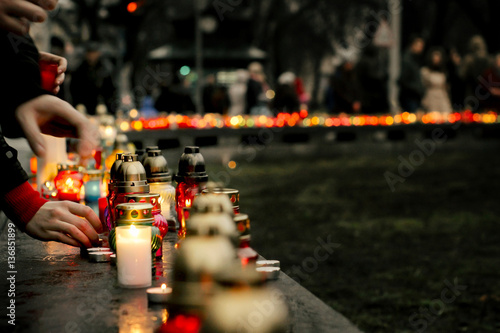 Fotografía  crowd of people lighting candles in city center, mourning victim