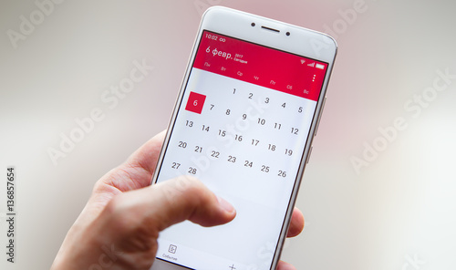 Fotografía  Hand with a smartphone with a calendar, one month plans