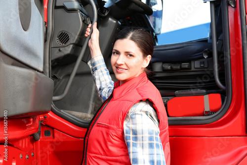 Fotografía  Young female driver near big modern truck outdoors