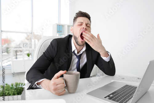 Tired business man yawning at workplace in office Poster
