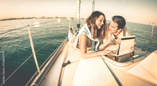 Young couple in love on sail boat having fun with tablet - Happy luxury lifestyle on yacht sailboat - Always connected people interacting with satellite wifi connection - Warm retro contrast filter