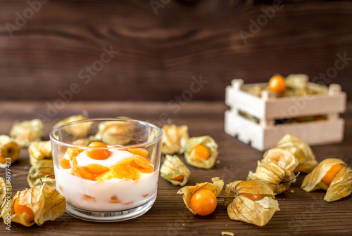 Poster yogurt with physalis on wooden background