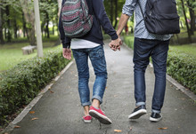 Low Section Of Couple Holding Hands Walking On Road