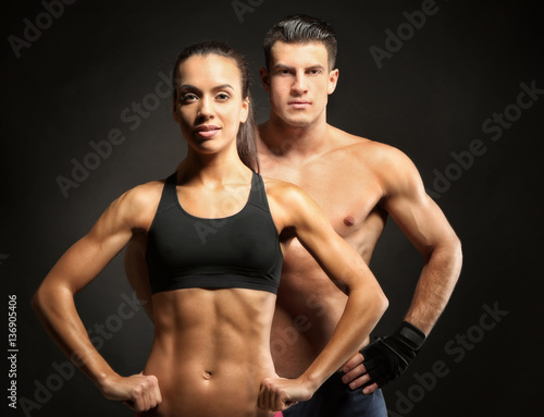 Spoed Foto op Canvas Fitness Sporty young couple on black background