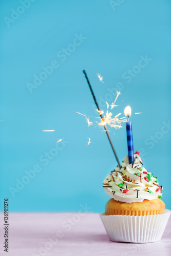 Photo  Birthday cupcake with candle and sparkler on color background