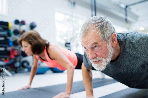 Photo Stands Fitness Senior couple in gym working out, doing push ups