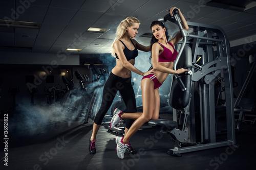 Obraz premium fitness, siłownia, kobieta, trening - Dwie piękne dziewczyny trenują na siłowni