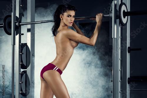 Naklejka premium fitness, siłownia, kobieta, trening - seksowna wysportowana dziewczyna trenuje na siłowni